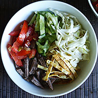 Раскладываем в тарелки отваренную лапшу, мясо, блинчики и овощную смесь, заливаем бульоном - фото