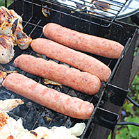 Поджариваем свиные сардельки на углях - фото